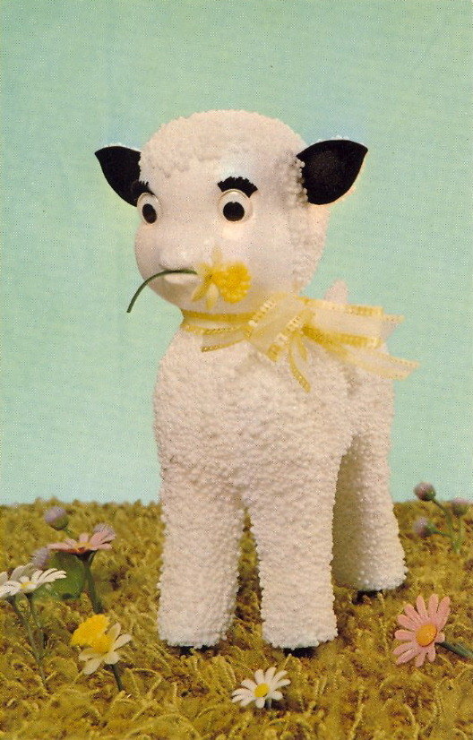 """SHY ANNE""     ""Please don't eat the daffodils."" Lovable Springtime lamb with big rolly eyes, perky ears and turned-up nose. Snow white plastic puffs add unbelievable realism. Standing over 9"" tall, she'll steal your heart. Another original creation from the studios of National Handcraft of Des Moines.     Gag me with a daffodil."