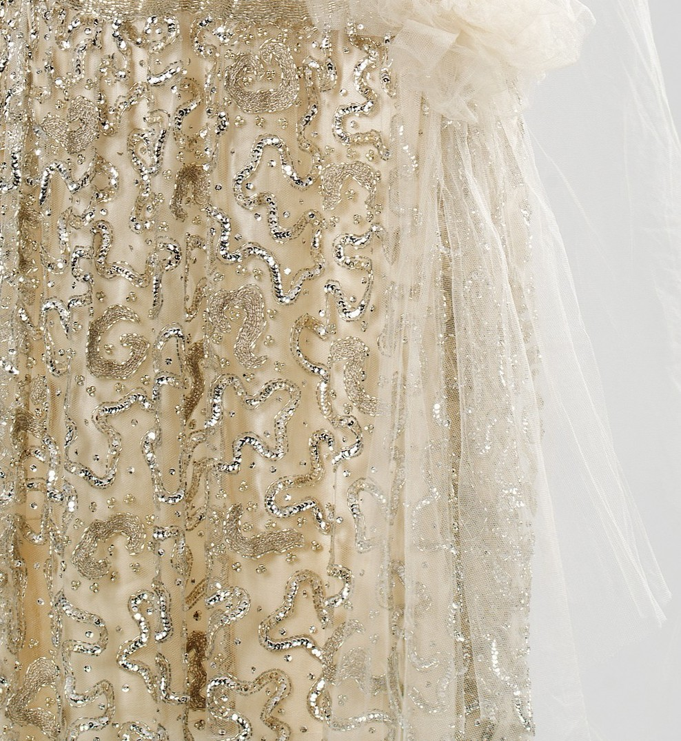 fashioninhistory:  Evening Dress (Detail) 1925 This piece is visually appealing because of the various textures and patterns created by the surface decoration. The detailed beadwork is quite stunning and would catch the light as the wearer was in motion. To add a feminine touch, the tulle bow has been added at the waist, and the extra fabric drapes over the shoulder.
