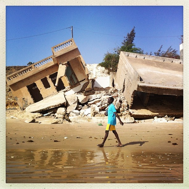 everydayafrica:  A man walks passed two homes that have collapsed due to high tides and an eroding coastline in Popenguine, Senegal. Photo by Jane Hahn @janehahn  #popenguine #senegal #coastline #coastalerrosion #beaches #beachhouse #tides #environment #globalwarming #iphoneonly