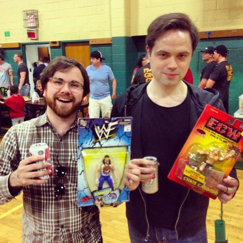 Two grown men at the wrestling show with their toys! (at St. Sebastian's Parish Center)