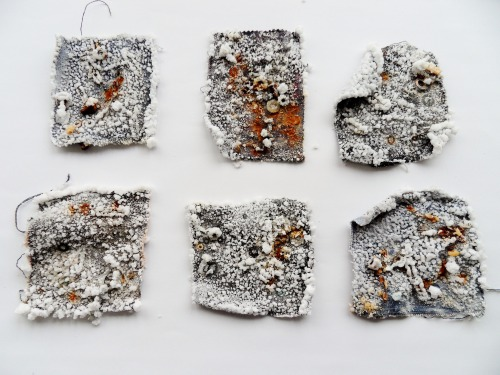 Denim Project - Rust and crysltalised salt. Exploring and experimenting with rust as a medium for mark making against denim. The rusted orange marks are representative of the coloured stitching used on denim jeans. Each piece produces its own unique and unpredictable composition as it dries. The process begins with submerging fabric in salt water and vinegar, an aid to corrode the metals faster. A selection of found metal objects is then placed on top and the mixture is left until completely evaporated. As the metals corrode a murky orange mark is left against the fabric, broken up by the crisp white of the salt which becomes crystallised during the evaporation process. On this small, fragile scale the appearance of rust is changed and becomes precious and delicate. Exhibited at Nexus Art Cafe, Manchester  http://re-consideredtheunwanted.blogspot.co.uk/2012_12_01_archive.html http://sarahelizabethwalton.blogspot.co.uk/