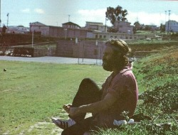 palace-of-exile:  1971- Jim Morrison sitting on hill in Redondo Beach (South Bay) putting Adidas on. Originally from Frank Lisciandro's 'A Feast of Friends'.