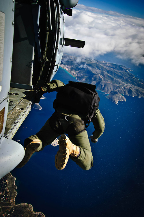 "A Sailor assigned to Naval Special Warfare, U.S. Special Boat Team, jumps out of the MH-60S Sea Hawk helicopter ""Ghostrider 53"", assigned to Helicopter Sea Combat Squadron (HSC) 28, Det. 1, as it flies over Megara Army Airfield as during the final day of a multi-week joint exercise."