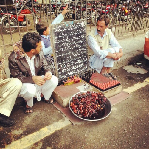 Street herbal medicine vendor. (at Nisbat Road, via umalik) Sign details that he is selling a unqiue oil of 40 herbs which can solve all sort of pains, stroke, skin rash and what not. Small bottle for 20 Rs and larges one for 50 Rupee. Oh and that if you can prove him wrong you will get a 500 Rupee reward!  Follow us on Facebook | Twitter or Submit something or Just Ask!