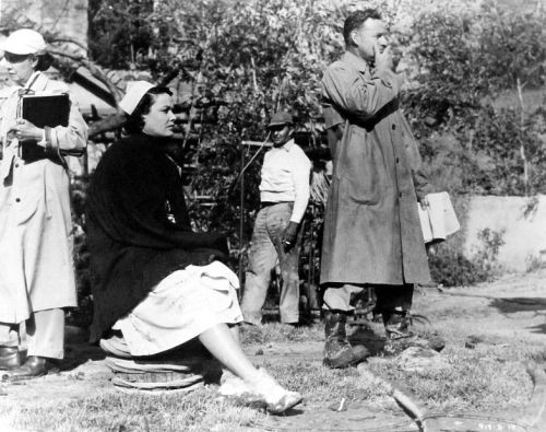 Gene Tierney and director Edward Dmytryk between scenes of The Left Hand of God