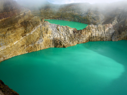"adapto:  The lakes of Mount Kelimutu -  Kimmberly, Dyllan Pollock & Simon S  Indonesia are considered to be the resting place for departed souls, the lakes are locally referred to as ""the lake of evil spirits"". All 3 lakes change colour from blue to green to black or red unpredictably."