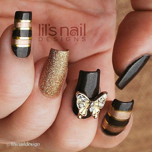 Super #pretty #tapemanicure by @lilsnaildesign ft. a blinged out #butterfly #nailcharm. Love the black & #gold!