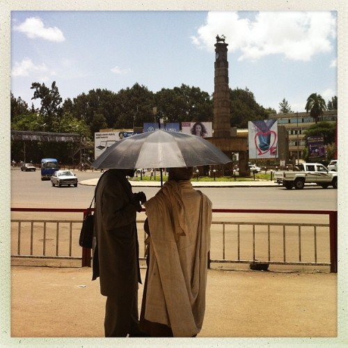 Two men have a conversation under an umbrella in Addis Ababa, Ethiopia. Photo by Jane Hahn @janehahn #addisababa #ethiopia #umbrella