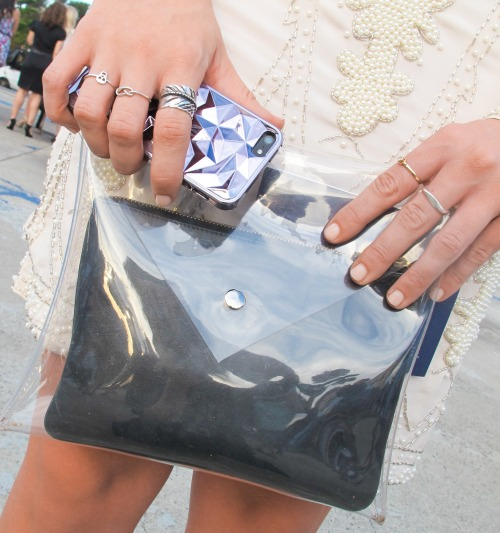 We love this combo of clear pouch, dainty rings and faceted iPhone case. Curated to perfection at #lmff! WGSN street shot, L'Oréal Melbourne Fashion Festival