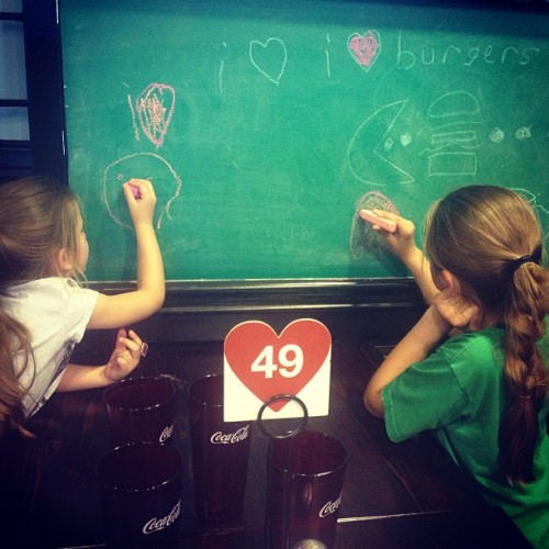 Pretty rad idea to have a chalkboard at the table. Keeps the kiddos entertained.  (at I Love Burgers)