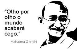 Imagem da semana: 'Olho por olho, o mundo acabaria cego' A nossa imagem da semana traz um convite à reflexão: em 2 de outubro se comemora o Dia Internacional da Não Violência, em homenagem à data de nascimento de Mahatma Gandhi. Num mundo repleto de tanto ódio (nas ações e discursos), guerras e destruição, este é um bom momento para refletir sobre os ensinamentos e sobre a trajetória de vida do líder indiano, que mostrou como protestos pacíficos podem realizar mais do que a agressão militar. Nascido na Índia em 1869, Gandhi é considerado um dos principais expoentes do pacifismo e da luta pelo respeito e realização dos direitos humanos e da justiça. Depois de estudar na Inglaterra e da passagem pela África do Sul, onde liderou um movimento pacifista, voltou ao seu país natal, tornando-se a principal figura do processo de independência da Índia, então uma colônia britânica.  Durante quase quatro décadas, lutou contra a opressão da metrópole utilizando como base para suas ações o satyagraha (princípio da não agressão, forma não violenta de protesto). Liderou a resistência pacífica por meio de marchas, petições, greves de fome, boicotes sistemáticos aos produtos ingleses e desobediência civil, com a violação organizada e sistemática de leis consideradas injustas e o não pagamento de impostos. Além da resistência dos britânicos, que talvez intimidados pelas estratégias de Ganghi jamais tenham partido para uma repressão militar aberta, a rivalidade entre hindus e muçulmanos ajudou a retardar o processo de independência. Mas ela finalmente veio logo após o fim da Segunda Guerra Mundial, em 1947, apesar de o Reino Unido ter mantido assegurados seus interesses econômicos na região.  O conflito interno, no entanto, impediu que a região permanecesse unida, dando origem, também, ao Paquistão, e a uma violenta migração de hindus e muçulmanos em direções opostas das fronteiras. Os dois países, aliás, parecem não ter aprendido tanto com seu grande líder, uma vez que mantêm até hoj