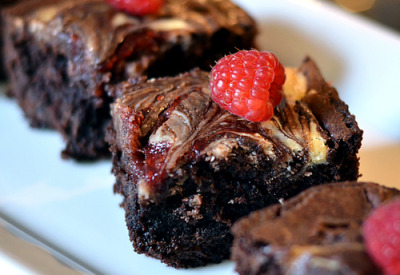 "prettygirlfood:  Raspberry Cream Cheese Brownies INGREDIENTS 1 box-mix of your favorite Brownies* 1 8-ounce block of Cream Cheese, softened 1/3 cup of Sugar 1 Egg 1/2 Cup Raspberry Preserves DIRECTIONS Preheat your oven according to your brownie recipe instructions. Prepare an 8×8 baking pan with cooking spray and set aside. Following the instructions for your brownies, mix the ingredients and pour into the prepared pan. In a mixer, cream together the cream cheese, 1/3 cup of sugar and 1 egg. You may need to scrape the sides and bottom of the bowl to allow the cream cheese to be fully incorporated into the mixture. Dollop the mixture over your brownie batter. Using a butter-knife, cut the brownie batter into the cream cheese mixture. Drag the knife in a swirling motion from one side of the pan to the other, making sure the knife goes all the way through the batter. Repeat until the two batters have a swirling, ""marble"" look. In a small bowl, measure the raspberry preserves and then stir vigorously with a spoon to thin down the jam. Dollop the preserves over the brownie-cream cheese batter and then, with a cleaned knife, swirl the raspberry preserves into the batter. Place the pan into your preheated oven and follow the brownie recipe's guidelines for baking times. Watch carefully toward the end to ensure the cream cheese doesn't get too browned. Allow to cool before cutting and serving.  NOTES *I love the Ghiradelli brownie mixes but any will do. You can also use a scratch-recipe."