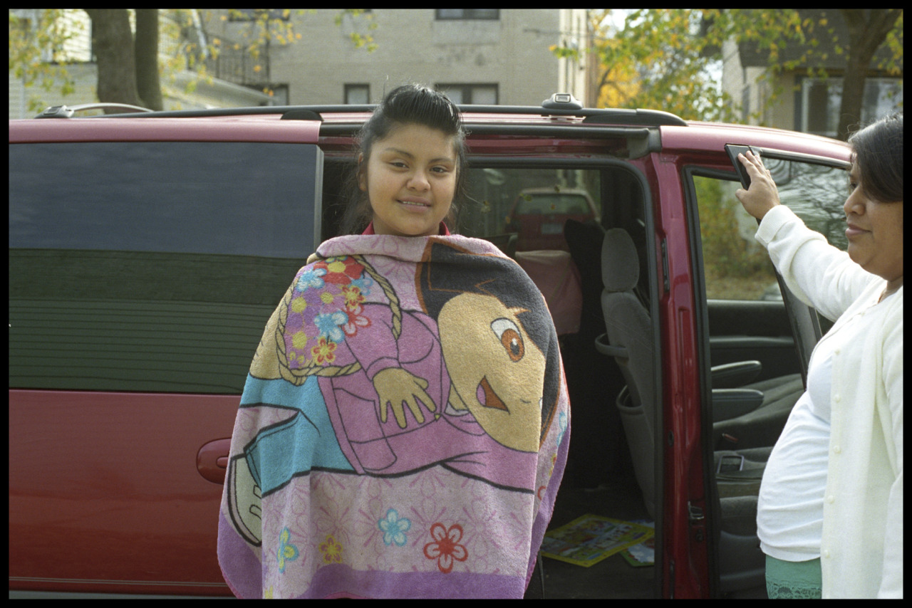 We are the Other - Young Girl Wrapped in Dora the Explorer Blanket, South Minneapolis, MN (2012) I think the meanings of a photo are the least clear when I'm actually taking it. I was photographing members of Light of Faith and Hope in Jesus Christ, a small storefront church where most, if not all, of the members are Latino. There were a variety of after-the-service-activities that I shot, including a birthday party, a pinata smashing, and basement buffet, before I saw this girl wrapped up in a cartoon character who really resembled her (as much as a real person can look like an oversimplified caricature of a human being). Over the years I've come to realize that I'm attracted to photographing the various ways people are mirrored (or not mirrored) culturally. I've never watched any episodes of Dora the Explorer, but when I was growing up there weren't any Asian cartoon leading characters, so I related to white characters like Jonny Quest and his father Race, rather than his brown exotic sidekick, Hadji. The World of Disney, I'm sure, had a lot to do in shaping my world and my view of myself. How long did it take to finally have a major cartoon character like Dora that reflected America's now-minority-but eventual-majority Latino population? Changing Lenses is the product of an ongoing conversation between eminent sociologist Doug Hartmann, Ph.D. and myself. In each post, we exchange what's seen behind a camera lens and what's seen through a sociological lens to get at the diversity of perspectives and cultivate a unique look at the human experience. Below is my perspective. Read Doug's reaction here.