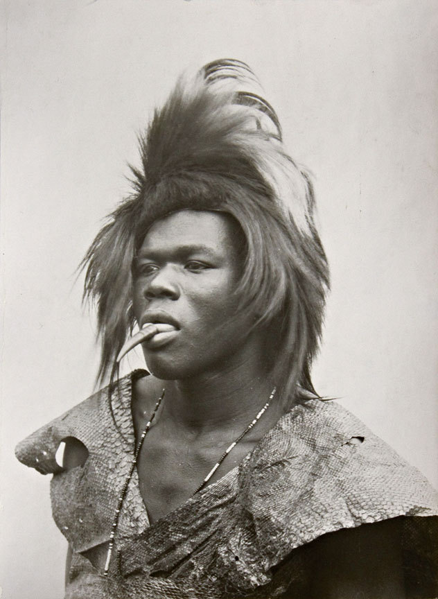Mozambique: A young Tsonga Khoka (snake dancer) in (then) Portuguese East Africa, 1933.  The dancer wears a python skin with a duiker's horn on the tip of his tongue to represent a snake's tongue. Photo by Alfred Martin Duggan-Cronin