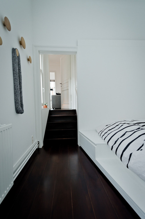 Source: My Scandinavian Home Loving the contrast between the rich dark floors and white white walls. The round coat hooks on the wall? You can pick them up from @Skandium. Perfect.