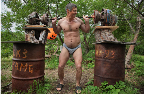 """Sergei Shurunov, head of a crack antipoaching team, muscles up with homemade weights at his camp in South Kamchatka Reserve. Aided by the WWF (World Wildlife Fund), his unit has nearly halted illegal fishing that was once rampant here."" http://www.rachelhulin.com/blog/2009/08/randy-olson-the-kamchatka-peninsula-and-national-geographic.html"