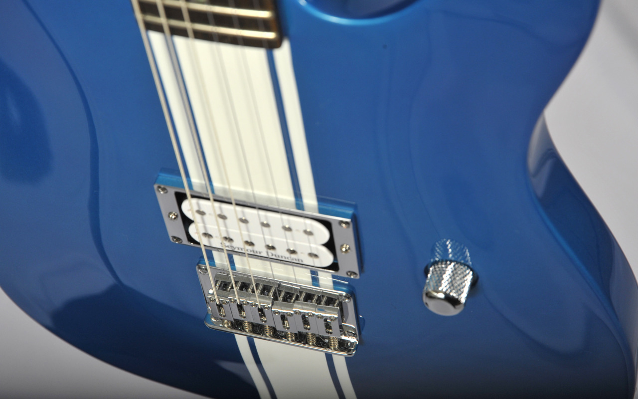 "guitar-porn:  2003 Fender Esquire Custom GT, nicknamed ""The Bitchin' Camaro"". Dan Amrich of the band Palette Swap Ninja sent us in some beautiful shots a while back and he's back with this particularly incredible specimen for us to to gaze at. ""Hi all! Been a while since I sent one of my guitars in, and I've been enjoying seeing everybody else's, so here's another one from my stash, thanks to my pro-photographer wife, KatrinAuchPhotography. These were Korean-made models that were sold for just the one year, then inexplicably blown out on clearance for $300 each. (Mine is Chrome Blue, and the finish varied a bit from light to dark over models I've seen; they also made these in metallic dark red with a white stripe and in silver with a black stripe.) It's an unusual Fender for a lot of reasons: Mahogany body, carved top, set neck, slim D-shaped neck profile, tummy cut, a lone volume knob…aside from the famous Telecaster shape, the hardtail bridge, and the single pickup configuration, it's about as far as a 50's Esquire as you can get! It was designed as a pop-punk monster, and it originally came with black chrome hardware and a black Seymour Duncan Invader SH-8. For personal preference, I dropped in a white SD JB SH-4, polished away the smoke tint from the tuners, and replaced the other parts with silver chrome. The stripe goes all the way around the body, even under the strap button. It's extremely light and makes a joyful noise! You can still find these floating around eBay from time to time for under $500, so if you spot one, grab it — you won't regret it.  Thanks for the daily dose of six-string lust. I'll send in more stuff later!"" Looking forward to it Dan!"