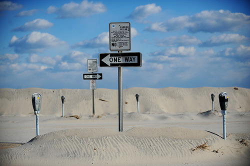 QUARTERED  Parking meters stand out from sand dunes at Seaside Heights, NJ, a town devastated by superstorm Sandy.  (Photo: Marko Georgiev / AP via The Guardian)
