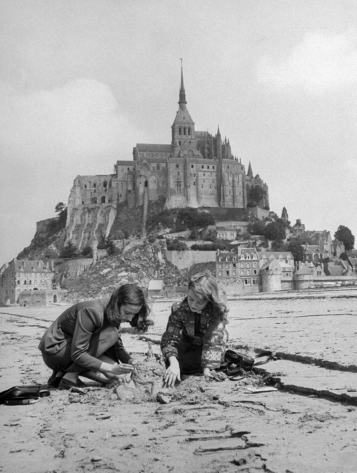 onlyoldphotography:  Yale Joel: American travelers building a sand replica of France's medieval abbey at Mont-Saint-Michel in the background, July 1948