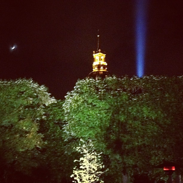The moon, the tip of the dome of Les Invalides and the spotlight from the Eiffel Tower seen from the garden of the Rodin Museum last night in Paris, France