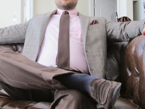 "Pairing this sportcoat with a pink shirt brings out entirely different undertones in the color than the blue shirts that I have paired it with in the past. The red geometric pattern on the pocket square also strengthens the warmth of the look. Navy socks: the universal sock. Brown wool glen check sportcoat. Pink OCBD. Brown knit tie. Brown silk square with a red geometric pattern. Brown chinos. 2"" cuffs. Brown suede loafers. Navy socks."
