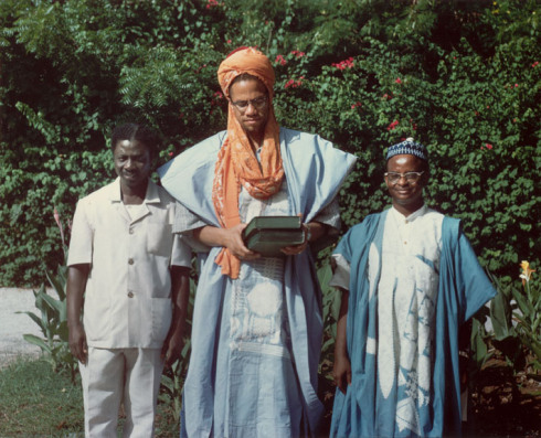 finethankyouandyou:  Malcolm in Accra, Ghana, May 1964, holding the Koran given to him by Alhaji Isa Wali, Nigerian High Commissioner to Ghana (right). Photo by Alice Windom.   Woop