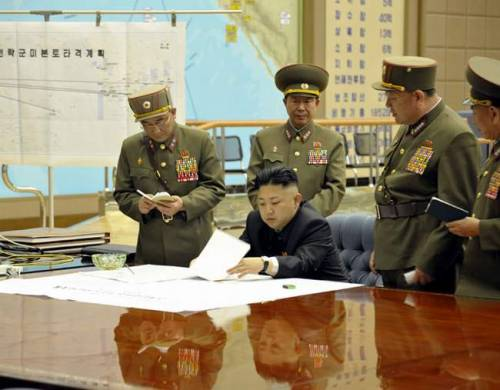 kim jung un looking at pieces of paper