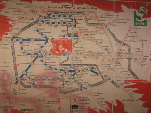 "transitmaps:  Historical Map: Berlin S-Bahn (c. 1955-1960) still at the ruined Siemensstadt station What an amazing photo! The Siemensbahn was part of Berlin's S-Bahn network from 1929 (when it was built as a short spur line to allow workers to commute to and from the Siemens factories in the area) to 1980, when it was shut down after a railway workers' strike. As seen on the map, the Siemensbahn is the short spur line just above and to the left of the large red area in the centre. The map is located (or was, in 2008, when the photo was taken) at the Siemensstadt station, which now lies in ruins and largely forgotten. The original poster of Flickr dates it to around 1980, probably based largely on the time the station closed. However, I date it to somewhere around 1955 to 1960 for a few reasons. Firstly, the map is pretty much hand-drawn and lettered. A map from 1980 would look more sophisticated, as this link shows. Many of the outer lines are still steam-powered (cross-hatched lines are marked in the legend as ""Mit Dampf…[torn]""). While borders between West and East Berlin (as well as the Greater Berlin area) are shown, and there's a clear colour differentiation between the two cities (blue for West Berlin, red for East), it's still possible to travel between east and west. Each station is marked with both the time it takes to get there from Siemensstadt and the price… and these markings continue into East Berlin. Therefore, the map's post-WWII, but before the Berlin Wall went up (1961). Comparing this map from 1955 and this one from 1960 shows that the outer ring line around the northwest of the city was completed some time between these dates. This line is shown on this map, although it's hard to see because of the damage to the map: this gives the best dating I can come up with without researching individual stations. Can anyone narrow it down even more? Another point of interest is the East Berlin station of Stalinallee, where someone has crossed out Stalin's name and replaced it with ""Frankfurter"", a reference to its pre-war name: Große Frankfurter Straße. This grafitti could have been added at anytime in the decades since the map was first put up, but the ""Stalinallee"" name also helps date the map, as the street was renamed as Karl-Marx-Allee in 1961. (Source: SnaPsi Сталкер/Flickr - definitely worth clicking through to the large version)"