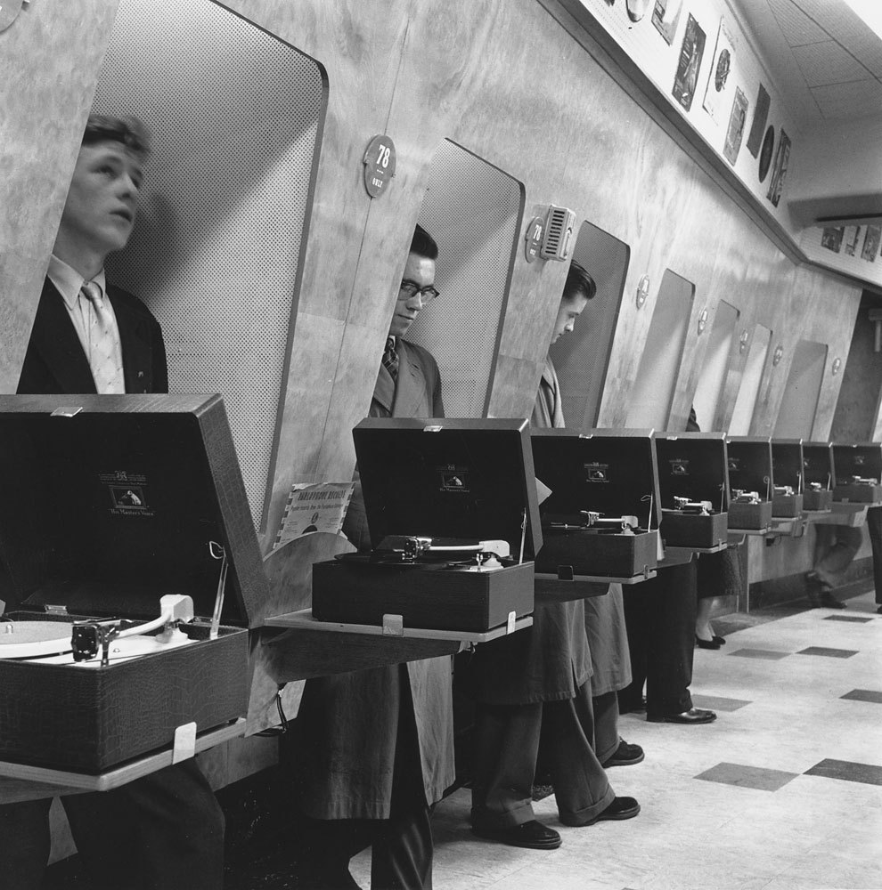 mikejrtaylor:  Customers at a London music store listen to the latest record releases in soundproof listening booths, 1955.