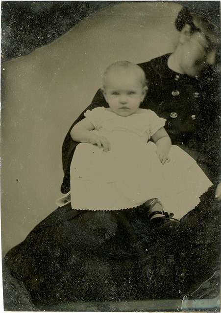A Shy Hidden Mother Revealed - Small Tintype Out of the Mat by Photo_History on Flickr.  Via Flickr: When the mat was removed from the small tintype we see the face of the woman holding the baby. She leans away and looks down. Perhaps it was an attempt to stay out of the frame although her large buttons still give her away.
