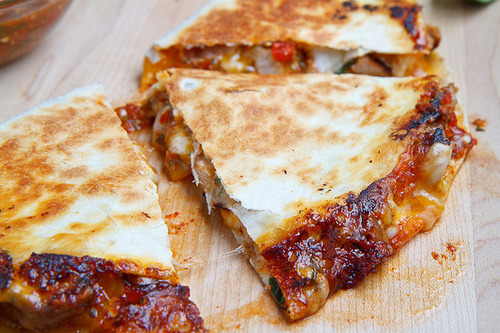 prettygirlfood:  Sweet Chilli Chicken Quesadilla Ingredients 1 tablespoon oil 1 small onion, sliced 1 (10 inch) tortilla 1/4 cup jack, shredded 1/4 cup cheddar, shredded 1/4 cup warm, cooked, shredded chicken or orange chicken bulgogi 2 tablespoons salsa naranja or sweet chili sauce 2 teaspoons toasted sesame seeds 1 tablespoon basil, torn 1 tablespoon cilantro, torn Directions Heat the oil in a pan over medium-high heat. Add the onions and saute until they start to caramelize, about 7-10 minutes, set aside and reduce the heat to medium Place the tortilla in the pan, sprinkle half of the cheese over half of the tortilla, then top with the onions, the chicken, salsa, sesame seeds, basil and cilantro and the remaining cheese. Fold the tortilla in half covering the filling and cook until the quesadilla is golden brown on both sides and the cheese is melted, about 2-4 minutes per side. Serve garnished with more salsa, sesame seeds and herbs.
