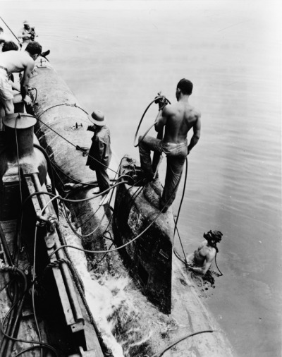 thekhooll:  Battleship.. Divers and crewmen of the U.S. Navy seagoing tug Ortolan fastening a midget Japanese submarine to the side of their ship, 1943.