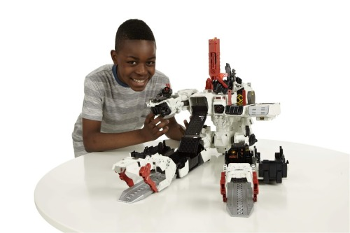 lifeinmyplasticbubble:  Behold Mighty Metroplex!!! Twenty-four inches of plastic robot fury! The largest Transformer ever made! Available this fall from Hasbro for around a hundred bucks! Holy shit! No idea who the kid is, though…