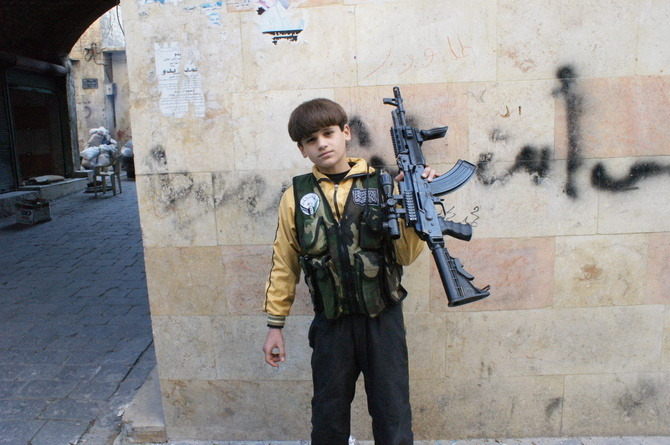 "Meet Syria's 11-Year-Old Killing Machine Mohammed Afar is 11 years old. The modified AK-47 assault rifle he carries stretches to nearly two-thirds his height. Over top of his faded yellow jacket a Free Syrian Army vest holds three extra clips, each full with live ammunition, and a walkie-talkie. An FSA badge sits on one side and a rendering of the Islamic Shahada, in Arabic calligraphy, on the other. He says he does not miss school or want to stay at home with his mother and two sisters. ""I want to stay as a fighter until Bashar is killed,"" he says, referring to Syrian President Bashar al-Assad. The fighters surrounding him, all claiming to be from Liwa al-Tawhid, pass him a sniper rifle and offer to take him to a frontline, so he can demonstrate his shooting. ""He is a great shot,"" says his father, Mohammed Saleh Afar. ""He is my little lion."" Over the course of its grinding 21-month insurgency, Syria's children have endured numerous abuses. Caught-up in shelling, airstrikes, and sniping, they have additionally been subject to arbitrary arrest, torture and rape, as reported by the United Nations Commission of Inquiry on Syria in August; which, additionally, noted ""with concern reports that children under 18 are fighting and performing auxiliary roles for anti-Government armed groups."" Both the Geneva Conventions and the U.N. Convention on the Rights of Children carry provisions that call for not using combatants under the age of 15, while the International Criminal Court's Rome Statute makes it a war crime. Continue"