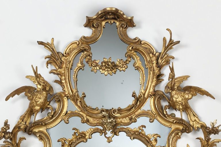 Chippendale  mirror  in an elaborate, oval frame of carved and gilt wood formed of symmetrical scroll-work.  Great Britain, UK  ca. 1765   Although here labelled as a mirror, this type of object in the 18th century was described as a girandole or sconce. The mirror glass reflects the candlelight to increase the volume of light. Here, the girandole frame has become a vehicle for elaborate Rococo carving, with flowers, leaves,  and birds (cranes often called ho-ho birds). The gilded carved surfaces also reflect candlelight.