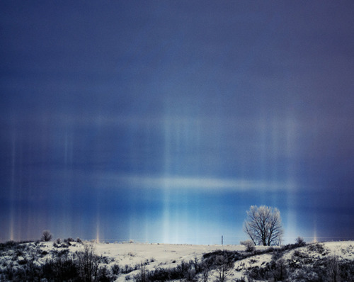 Multiple Light Pillars     The multiple vertical shafts pictured above are light pillars.      Whereas Sun pillars can be observed on occasion near sunrise and sunset, when sunlight glints off the undersides of ice crystals in cirrus clouds, these pillars have another light source; highway and shopping mall lights. In this case, the artificial lighting is being reflected off diamond dust falling just above the surface.      Diamond dust is ice (ice crystals) that forms when the air is very cold and the lower atmosphere is quite stable. With this type of precipitation, accumulation is negligible since little moisture is squeezed out of the cold, dry atmosphere. The temperature when I took this shot was about - 4 F (- 20 C) Note that a light pillar's color depends on the color of the artificial lighting.