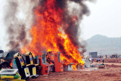asimplehistory:  Gambling Machines Burning - Xinhua/Landov Gambling machines are destroyed at the Renjiagou village of Shunqing District in Nanchong City, in southwest China's Sichuan Province. Local policemen destroyed some 1000 confiscated gambling machines.