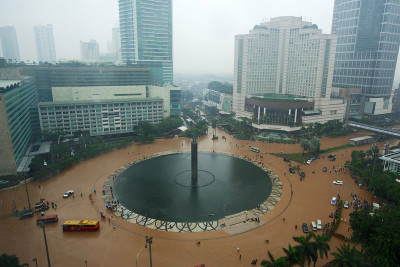 fotojournalismus:  People struggle through floodwaters in Jakarta's central business district on January 17, 2013 in Jakarta, Indonesia. Thousands of Indonesians were displaced and the capital was covered in many key areas in over a meter of water after days of heavy rain. [Credit : Ed Wray/Getty Images]