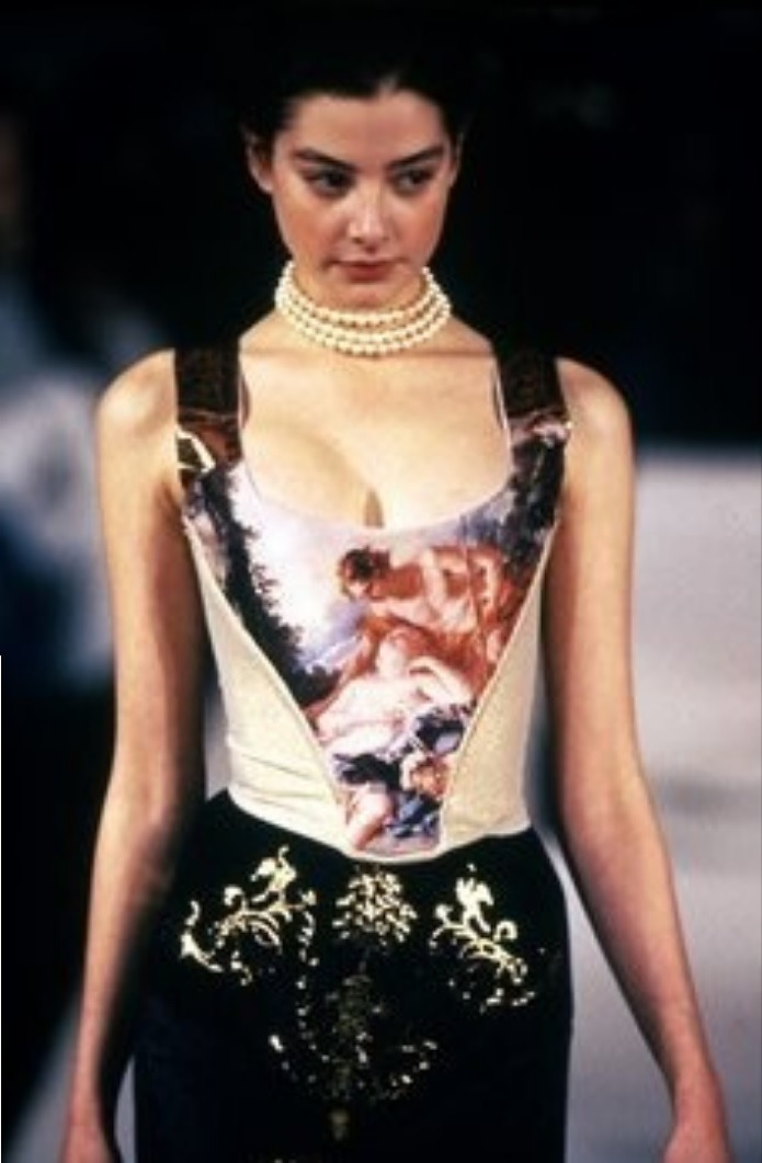 "Vivienne Westwood F/W 1990/1991 - ""Portrait"" For this collection, Westwood drew inspiration from oil paintings as a ""display of material wealth"". She printed images of paintings by Boucher - this one Shepherd Watching a Sleeping Shepherdess - onto her corsets, as well as taking literal inspiration in her designs from clothing featured in paintings by other artists (including Winterhalter and the 18th century painting The Boy with a Bat). She also drew ideas from the furniture of Andre Charles Boulle. The women in the show walked on platform shoes - ""putting [them] on a pedestal as though she had stepped out of a painting""."