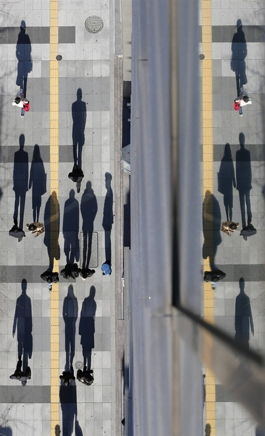 Tokyo, Japan: Pedestrians cast shadows on the pavement near the headquarters of the Bank of Japan   Photograph: Kim Kyung-Hoon/Reuters