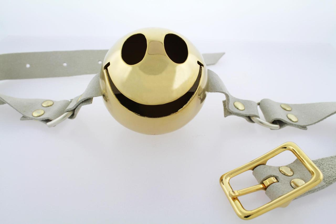 White leather and gold-plated smiley ball gag / Mallory Weston. For strong teeth.