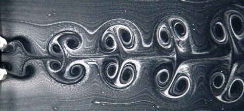 The von Karman vortex street of shed vortices that form the wake of a stationary cylinder are a classic image of fluid dynamics. Here we see a very different wake structure, also made up of vortices shed from a cylindrical body.  This wake is formed by two identical cylinders, each rotating at the same rotational rate. Their directions of rotation are such that the cylinder surfaces in between the two cylinders move opposite the flow direction (i.e. top cylinder clockwise, bottom anti-clockwise). This results in a symmetric wake, but the symmetry can easily be broken by shifting the rotation rates out of phase. (Photo credit: S. Kumar and B. Gonzalez)