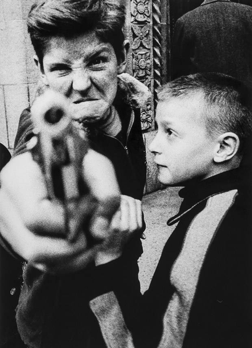 "Gun 1, New York, 1955 photographed by William Klein (x) ""… This seems to be considered my key image… It's fake violence, a parody. I asked the boy to point the gun at me and then look tough. He did, and then we both laughed… [I see it] as a double self-portrait. I was both the street kid trying to look tough, and the timid, good little boy on the right."""