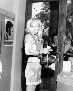 Italian singer Patty Pravo getting out of a shop and looking surprised. Rimini, 1969