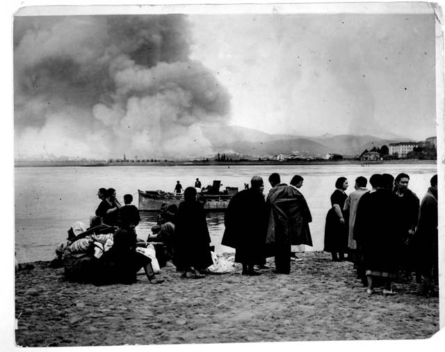THOUSANDS FLEE TO SAFETY FROM BLAZING IRUN. — With the few belongings they managed to take with them, strewn on the HENDAYE PLAGE, FRANCE these refugees from IRUN watch the town blazing with its shroud of smoke and gun fire. The kiddies in the foreground are blissfully ignorant of the fact that they are homeless and destitute and spend the time making sand castles on the safe French beach, last night.   September 1936HendayeKeystone View Company