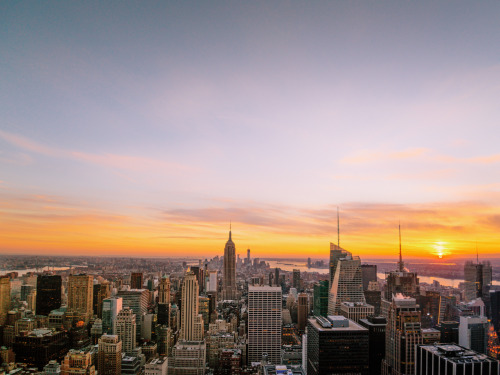 "nythroughthelens:  New York City sunset over the skyscrapers of midtown Manhattan. —- I never really get tired of this view. I know I have expressed that sentiment many times but it's absolutely true. There's something incredibly breathtaking that occurs when you are above the rooftops of the city. It's as if the city shrinks below a vast sky in a huge universe and everything that once seemed impossible seems effortless and within the realm of possibility. It's so easy to forget that sort of thing when you live in a large city like New York City. When you are in the thick of it all, it can feel like the you are alone in a never-ending maze of cavernous streets as everyone else's dreams and hopes fly past you at the speed of light. But when you take yourself out from the middle of everything and change your perspective, it's as if the city holds its arms out to you beckoning you to come back and put your own dreams out there so they can spread their wings and fly up to the sky towards the horizon leaving a trail of hope in their path. —- This was taken from the top of Rockefeller Center (also known as Top of the Rock) and it's probably one of the most popular views of the New York City skyline since it includes the Empire State Building and the skyscrapers of midtown Manhattan. The view is looking south towards One World Trade Center (also known as the Freedom Tower and 1 WTC) and the skyscrapers of the Financial District. —- View this photo with a comment thread on my Google Plus page —- View ""New York City Sunset - Skyline"" in my photography portfolio here, email me, or ask for help."