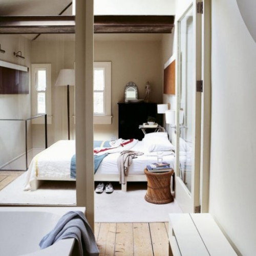 designed-for-life:  Open-plan light bedroom The glass wall, separating the ensuite bathroom and bedroom, creates both a sense of space and light. Here, the ceiling has also been opened up into the loft for a greater effect.