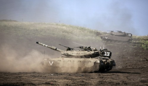 An Israeli Merkava tanks maneuver rolls during a drill in the Israeli annexed Golan Heights near the border with Syria on May 6, 2013. UN chief Ban Ki-moon has appealed for restraint after Israeli air strikes on targets near Damascus which prompted Syrian officials to warn 'missiles are ready' to retaliate.