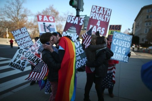 Gay Couples Kiss in Front of Westboro Baptist Church Protesters  WASHINGTON, DC - MARCH 27: Two same sex couples kiss in front of Westboro Baptist Church protesters, at the U.S. Supreme Court, on March 27, 2013 in Washington, DC. Today the high court is scheduled to hear arguments on whether Congress can withhold federal benefits from legally wed gay couples by defining marriage as only between a man and a woman.  (Mark Wilson / Getty via Huffington Post)