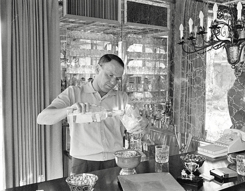 Frank Sinatra pouring a drink at his home bar, in 1965 John Dominis